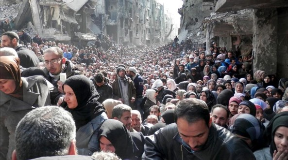 FILE - This file picture taken on Jan 31 2014 and released by the United Nations Relief and Works Agency for Palestine Refugees UNRWA shows residents of the besieged Palestinian camp of Yarmouk queuing to receive food supplies in Damascus Syria An international advocacy group accused the United Nations of not being neutral in the Syrian conflict in a trenchant report on Wednesday June 15 2016 claiming the world body is prioritizing its relationship with the Damascus government over delivering aid to civilians UNRWA via AP File